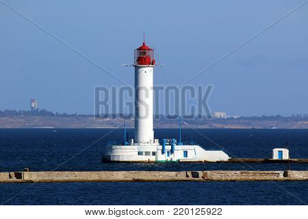 Vorontsov Lighthouse Ukraine the gulf of Odessa. Sunny day landscape with sea skyline seamark. Odessa red and white lighthouse in bright sunny summer day in the middle of the Black Sea. Blue sky and calm water