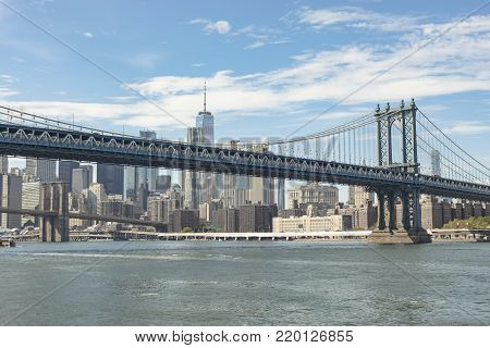 View of the Brooklyn and Manhattan bridges over the Hudson river with skyline of Lower Manhattan in New York City, USA.