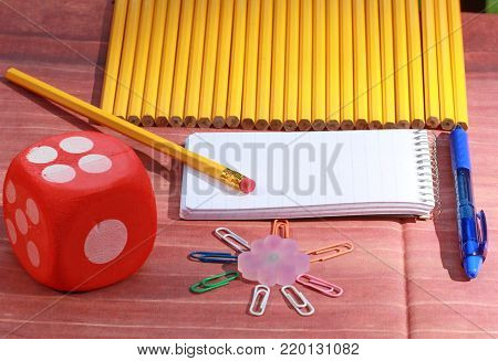 School supplies of pencils, clips, erasers, a writing pad and a dice.