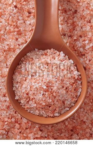 Pink Himalayan salt in spoon. Top view of spoon full of pink Himalayan salt on salt crystal.