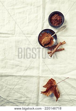 Ground cinnamon, cocoa powder and cinnamon sticks on white linen cloth
