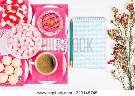 Cup of coffee, donut, tasty snacks, notebook, pencil and flowers