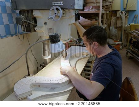 ST. PETERSBURG, RUSSIA - AUGUST 8, 2017: Worker making eyelets for strings of harp using drilling machine in Resonance Harps enterprise. It revives the production of harps of the Lunacharsky factory