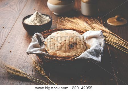 indian bread / Chapati / Fulka / Gehu Roti with wheat grains in background. It's a Healthy fiber rich traditional North/South Indian food, selective focus