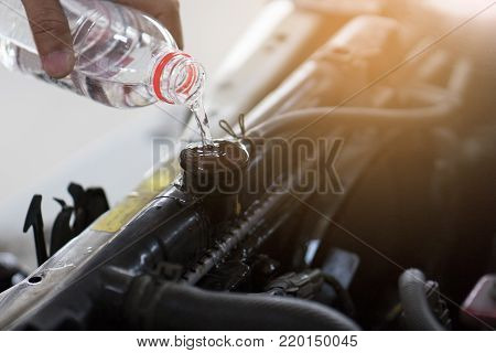 Hand pouring water for radiator in car. Because of the heat is due to some deterioration.