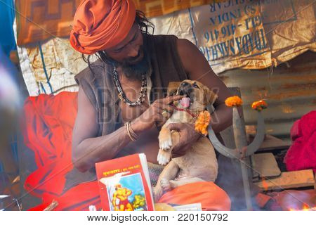 BABUGHAT, KOLKATA, WEST BENGAL / INDIA - 10TH JANUARY 2015 : Hindu Sadhu cudding a puppy, baby street dog.