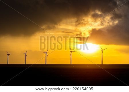 Beautiful sunset over the windmills on the large field