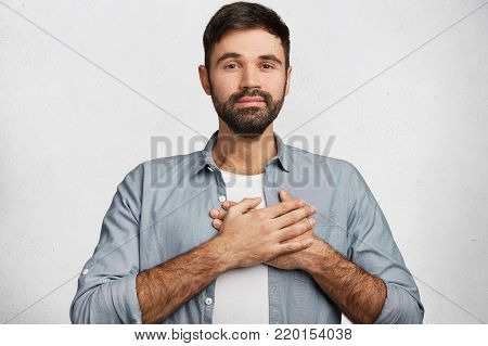 Pleased Handsome Male Expresses His Positive Feeling To People Who Surround Him, Keeps Hand On Chest