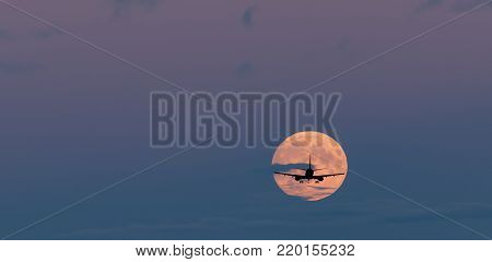 Silhouette of landing airplane at dawn on background of the moon