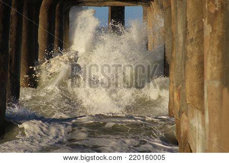 Winter storm waves crashing through pilings at Manhattan Beach pier, Los Angeles, California.