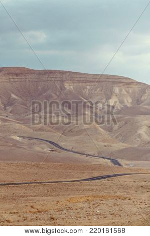 Vertical photo landscape view on desert road in judean negev desert in Israel. Dry summer sunny empty valley with sand, mountains, rocks and stones. Horizon sky and clouds