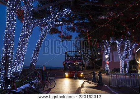 Monaco - November 16 2017 : Hop On Hop Off city tour bus on the square Place du Palais decorated by Christmas in the evening in Monaco-Ville, Monaco