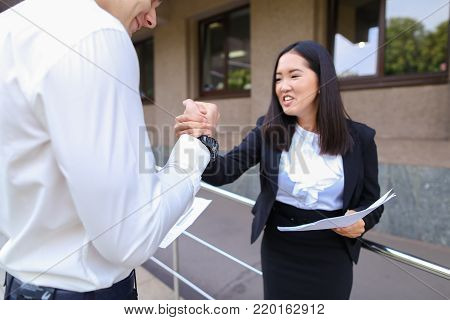 Two people team group young asian businesswoman explain caucasian male man businessman dressed in suits look at documents , make deal and shaking hands  outside. Man dressed in black  trousers and white shirt, girl dressed in white blouses and black class