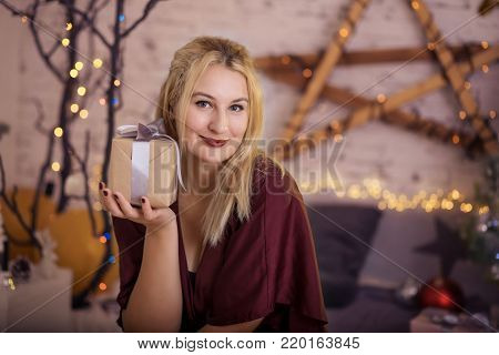 Happy woman with gift near a Christmas tree