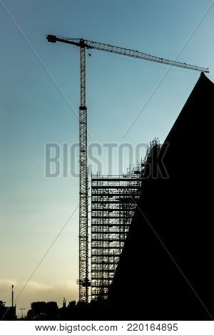 silhouette scaffolding building construction crane, black profile structure of scaffolding sunset at city, architecture engineering diagonal building structure