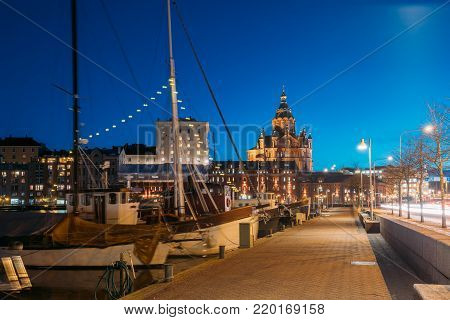 Helsinki, Finland. Pier With Boats, Pohjoisranta Street And View Of Uspenski Cathedral In Evening Night Illuminations.