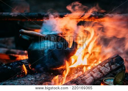 Black Old Retro Iron Camp Kettle Boiling Water On A Fire In Forest. Bright Flame Fire Of Bonfire At Dusk Night.