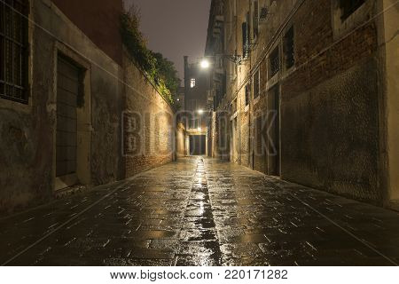 empty rainy street by night in Venice, Italy