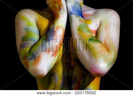 Body art. Drawing on the body. Beautiful girl with painted body watercolors. A white young girl painted the body with paint.