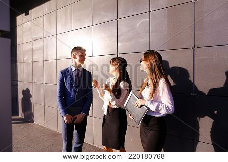 Modern handsome male man and two pretty confident girl, successful young office workers, businessmen, students communicate, laugh, rejoice successfully concluded transaction, end working day, talk on various topics, discuss working moments