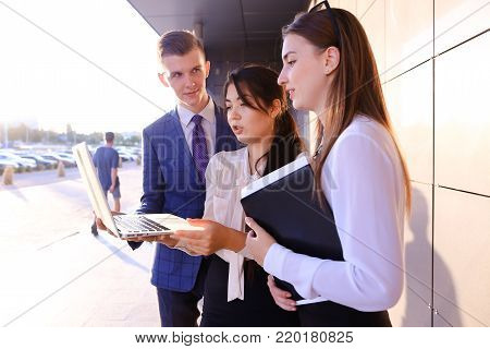Modern young man and two attractive smart young women, business people, students communicate, holding laptop and study work plan, familiarize with presentation, teach each other new programs, solve important problems and workloads