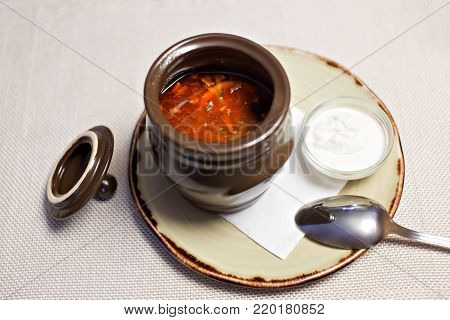 Solyanka - Russian traditional meat soup. Russian soup saltwort in round plate on wooden background.