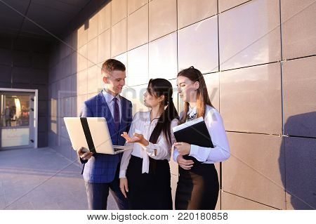 Modern young man and two attractive smart young women, business people, students communicate, holding laptop and study work plan, familiarize with presentation, teach each other new programs, solve important problems and workloads holding folder with docu