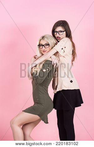 Fashion, style, vogue. Women with long hair in geek glasses. Beauty, look concept. Girls pose in torn clothes on pink background. Visage, makeup, hairstyle.