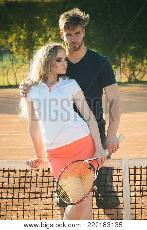 Relationship, relations, family. Couple in love stand at tennis net on clay court. Sport, game, match concept. Woman and man athletes hold tennis racket. Activity, energy, health.