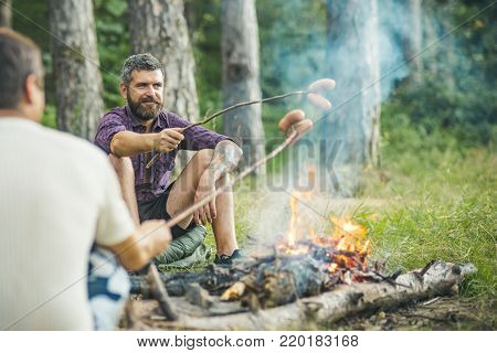 Summer camping, hiking, vacation. Friends men roast sausages on sticks on campfire in forest. Picnic, barbecue, cooking food concept.