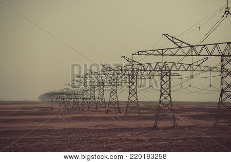 Power line towers in desert on grey sky background. Global warming, climate change. Electric energy transmission. Ecology, eco power, technology concept. Electricity distribution stations.