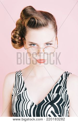 Girl in stylish vintage dress on pink. Beauty and fashion, teacher. secretary, hairdresser and cosmetics. pinup, youth and look. Woman with retro hair and fashionable makeup in glasses, pinup.