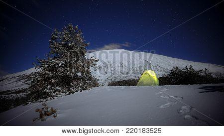 night stars on illuminated yellow tent on the snow and Etna Mount, Sicily