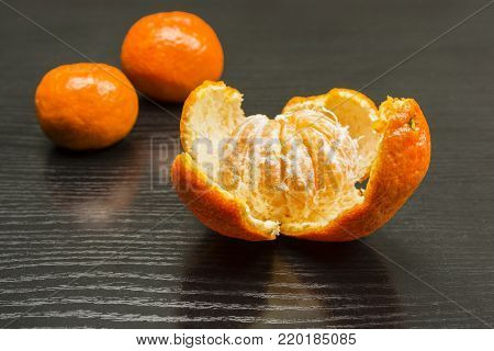 Removed peel from the ripe fruit of a sweet mandarin on the table.