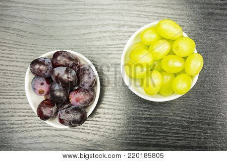 Grape variety white and red in separate bowls on a wooden table, view from above..