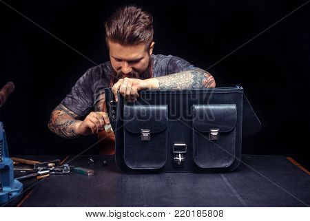 Craftsman professionally making black expensive leather briefcase