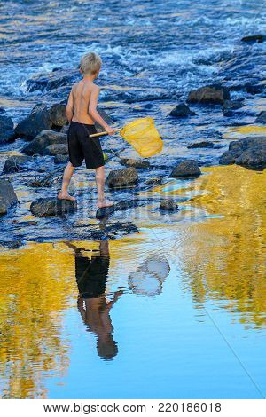blond haired boy fishing for crayfish in the Boise River, Boise, Idaho, USA