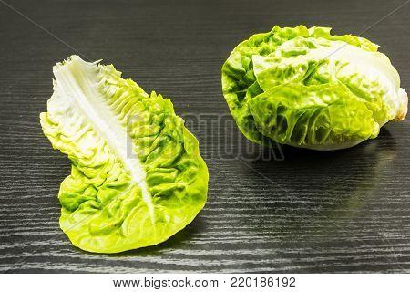Mini romaine lettuce leaf on a wooden table.