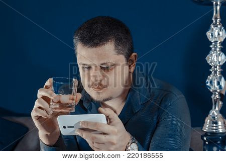 A young man is reading a message on a mobile phone and is holding a glass in his hand. Night club. Hookah next.