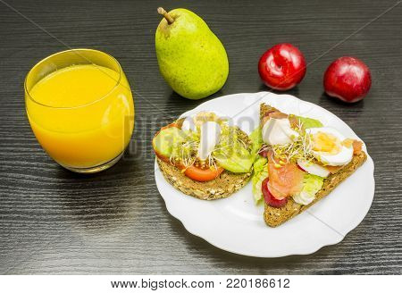 Vitamins and minerals for breakfast. That means healthy rye bread sandwiches with vegetables, salmon, eggs and mayonnaise. Fruit for a snack and a glass of orange juice to drink.