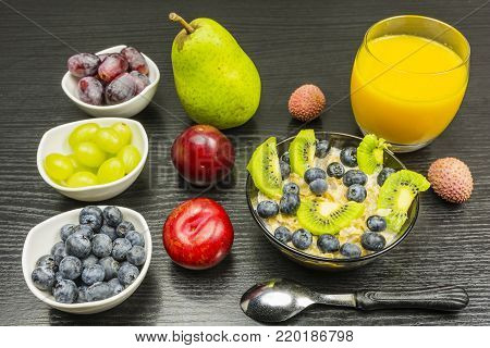 Tasty and healthy breakfast - Oatmeal in milk with blueberries and kiwi. In addition, fruits such as pear, plum, lychee, grapes and orange juice.