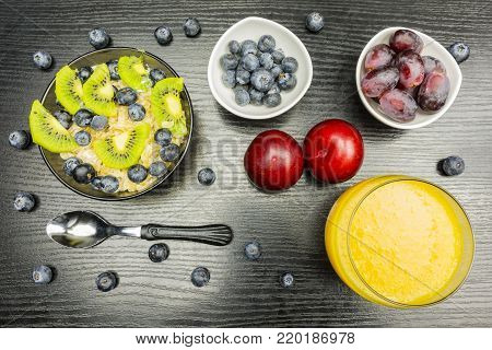 Healthy breakfast for children and adults. Oatmeal on milk with fruit, extra fruit for a snack and a glass with orange juice for drinking.