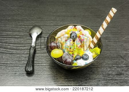 Dessert - ice cream with whipped cream, chocolate and fresh fruit, garnished with a sweet tube and sugar decorations.