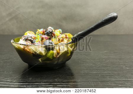 Teaspoon immersed in a bowl with ice cream dessert on a wooden table.