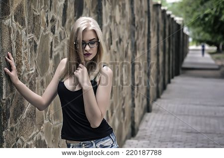 Beautiful pretty girl against background of brick wall with green leaves
