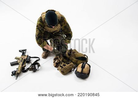 Top view soldier putting ammunition in pocket of bulletproof vest. Assault rifle and helmet locating near him. Munitions concept. Copy space