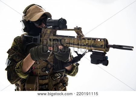 Portrait of calm soldier looking at sniper scope while keeping assault rifle in hands. Military concept, Isolated