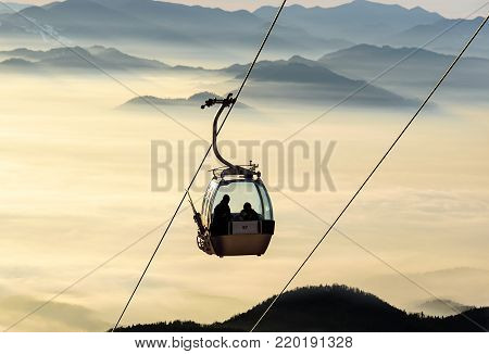 Ski lift cable booth or car, Ropeway and cableway transport sistem for skiers with fog on valley background .