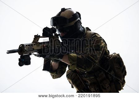 Portrait of serious soldier looking at sniper scope of modern weapon. Army concept. Isolated