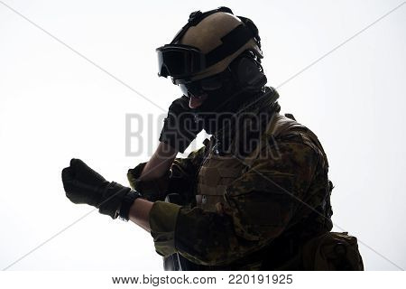 Side view serious peacemaker looking at watch while speaking by portable radio set. Army and communication concept
